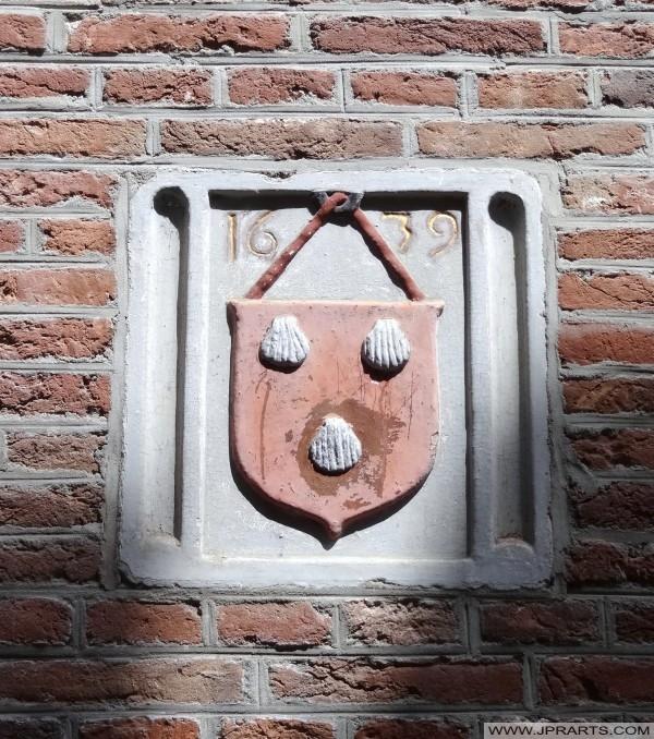 wapen van de familie Oosting (drie witte coquilles op een rode achtergrond) - Assen, Nederland