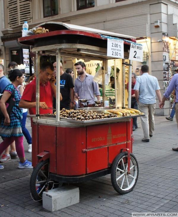 vendedor ambulante Vende castañas recién asadas y maíz asado en Estambul, Turquía