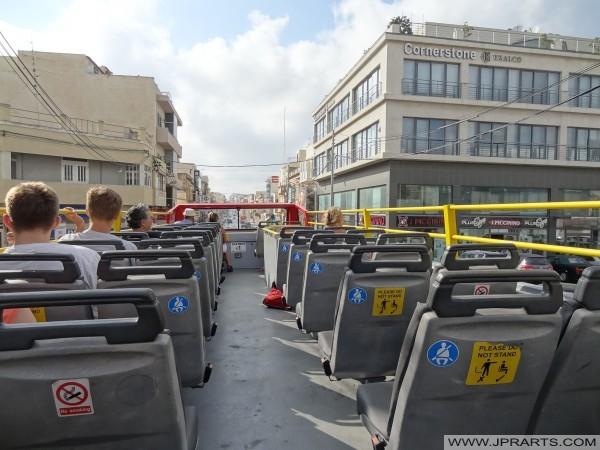 Hop on Hop off autobus projede budovu Cornerstone Business Centre v Mosta, Malta