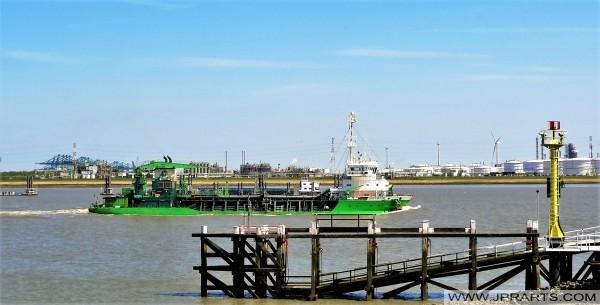 Dubbelschroef Sleephopperzuiger Artevelde en op de achtergrond Oiltanking Antwerpen (Stolthaven) aan de Schelde (Belgium)