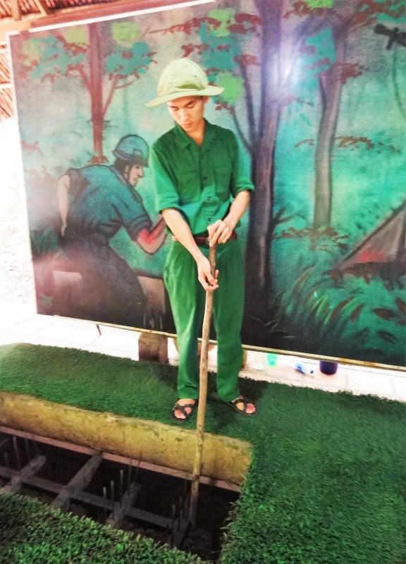 Uniformed Führung Gebraucht Bambuspfosten, zum der Auslösung der Vietcong Fallen zu demonstrieren (Củ Chi Tunnel, Ben Dinh, Vietnam)